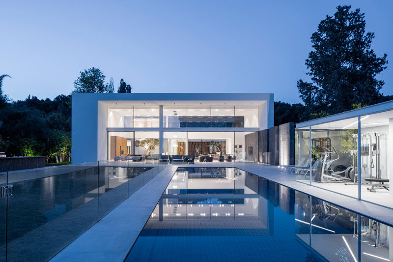 This Israeli house has a large backyard with a large lawn, swimming pool, outdoor patio with dining table and lounge, as well as sun lounges and a gym.