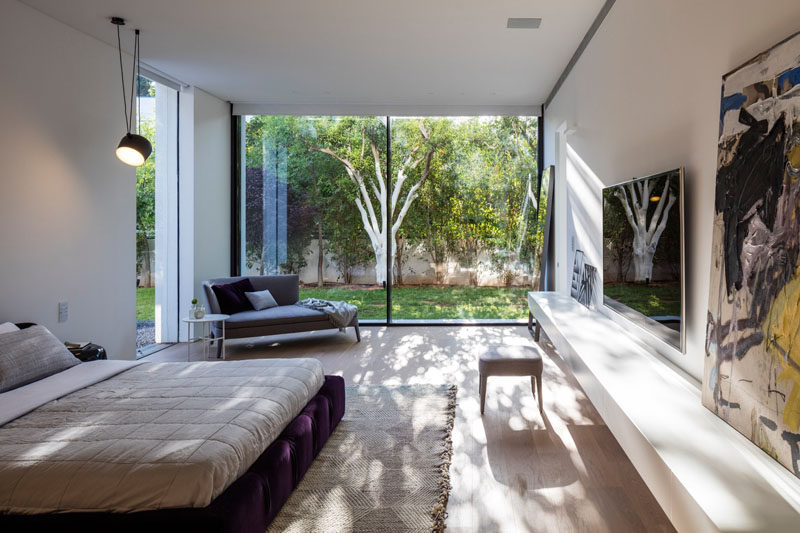 This bedroom has a view of the garden through floor-to-ceiling windows, and a low shelf for displaying artwork.