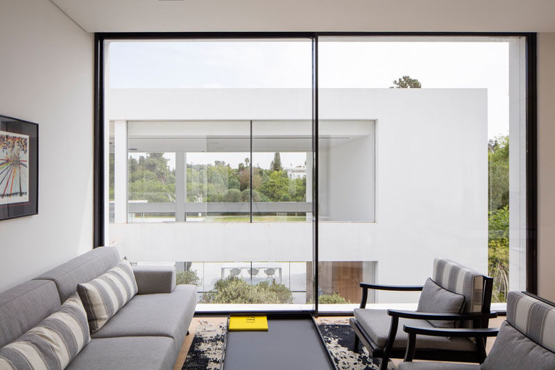 This sitting room has large windows that take up the entire wall and let an abundance of natural light into the room.