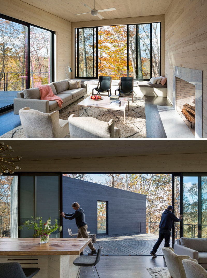 This living room has built-in bench seating under the window, and large doors with black frames can be slid open to provide access to the deck.