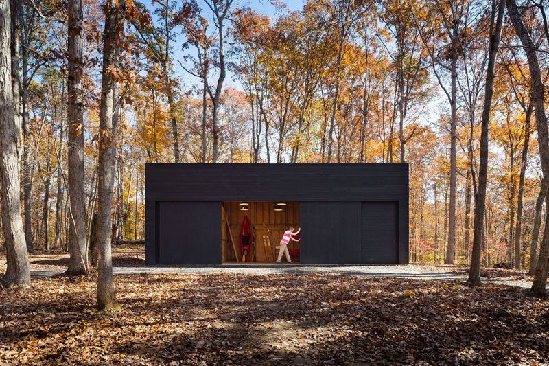 This home in a wooded area has a separate garage/studio that matches the design of the house.