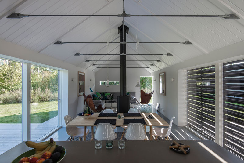 Inside this modern barn, the living, dining and kitchen area all share the same space. White vaulted ceilings and walls give the room a light and lofty feeling.