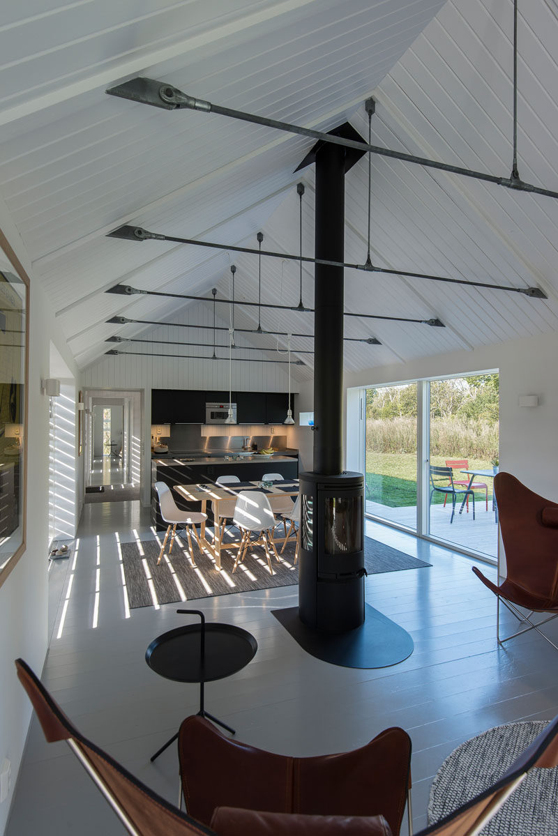 The black kitchen cabinets in this modern barn match the centrally located black fireplace.