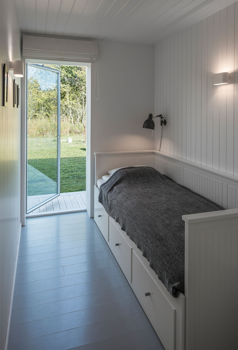 In this small bedroom, white wood paneling on the walls and ceiling make the room appear larger, and there's also has a door to the garden outside.