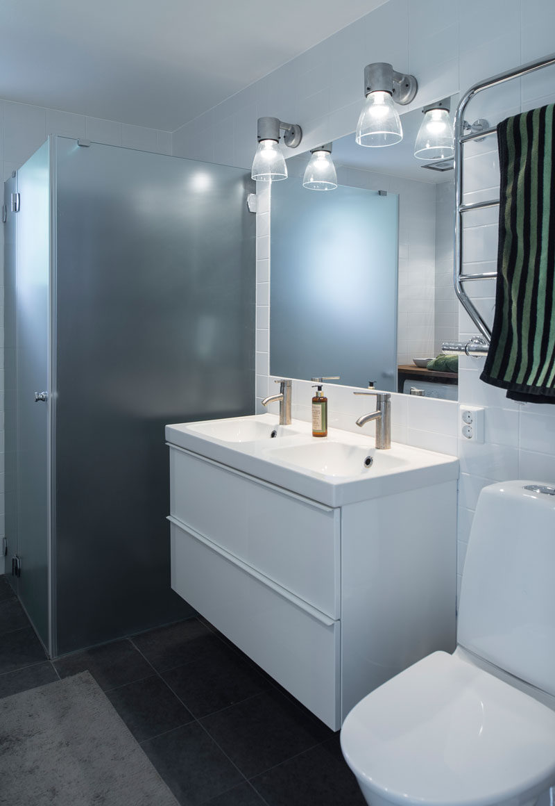 In this bathroom, white walls and cabinetry contrast with the dark floor, and there's a frosted glass shower enclosure.