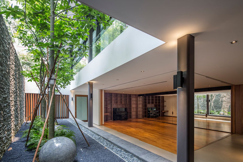 This home has a multi-purpose room that opens to a small landscaped area with tall trees.