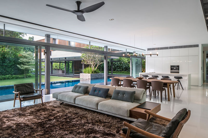 In this open-plan Singaporean home the living , dining and kitchen areas all open up to the pool and garden outside.