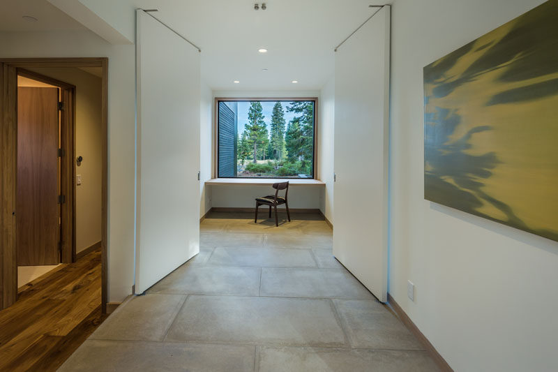 This home office with a built-in desk has a large picture window with views of the trees outside.