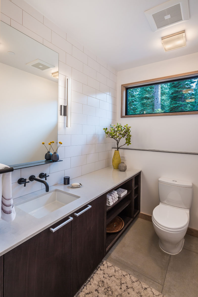White subway tiles and a dark vanity with some open shelves have been used in the design of this bathroom