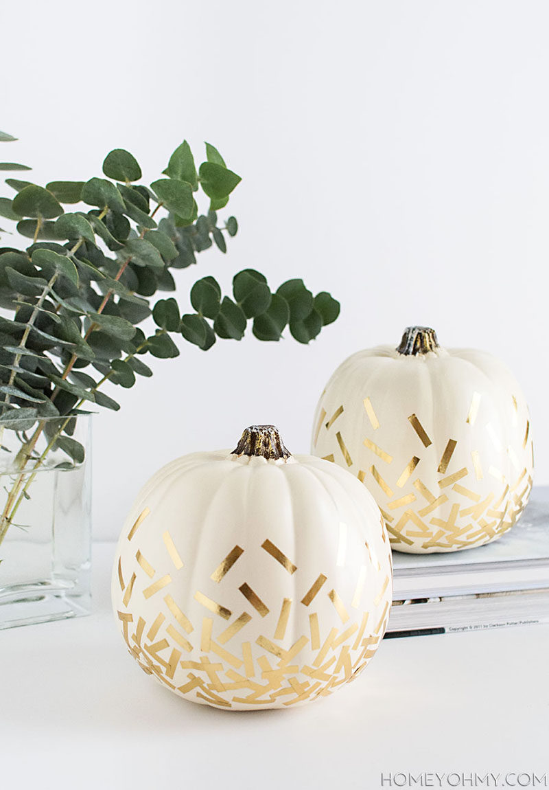 13 Modern DIY Halloween Pumpkin Ideas // White pumpkins with gold confetti made from washi tape makes for minimal, stylish, and simple no-carve pumpkin decor.