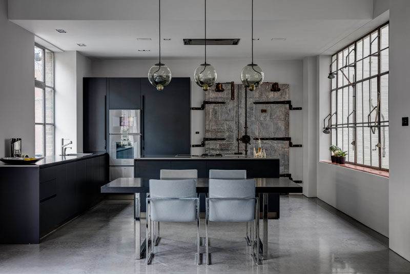 In this kitchen an industrial door, from when the building was a shoe warehouse, has been left, and the black cabinetry contrasts the white walls and polished concrete floor.