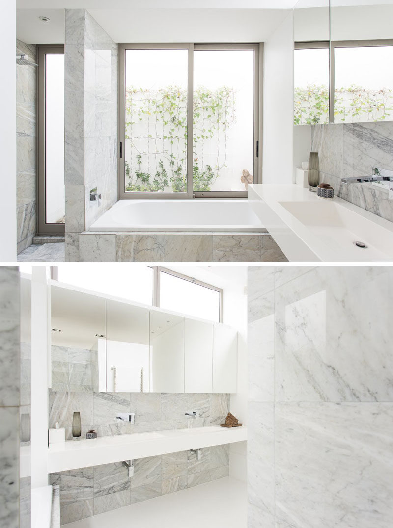 Lots of windows and the light color of the marble used on the walls, floor, and backsplash keep this bathroom feeling bright and airy.