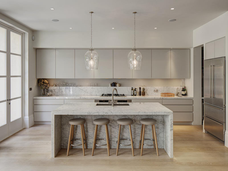 Kitchen Design Idea - How To Add Marble In Your Kitchen // Light grey kitchen cabinets compliment the flecks in the marble and create a sophisticated feel in this bright and airy kitchen.