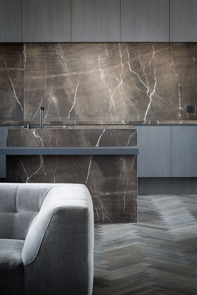 Kitchen Design Idea - How To Add Marble In Your Kitchen // The dark marble island, countertops, and backsplash in this kitchen coupled with the dark floor and dark cabinetry create a sophisticated, timeless spot to prepare meals and entertain guests.