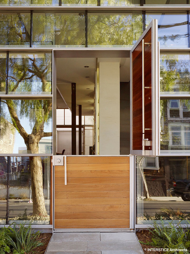 Door Design Ideas - 9 Examples Of Modern Dutch Doors // This modern Dutch door, surrounded by walls of windows, opens up the front of the home and allows in natural light and lets fresh air flow into the home.
