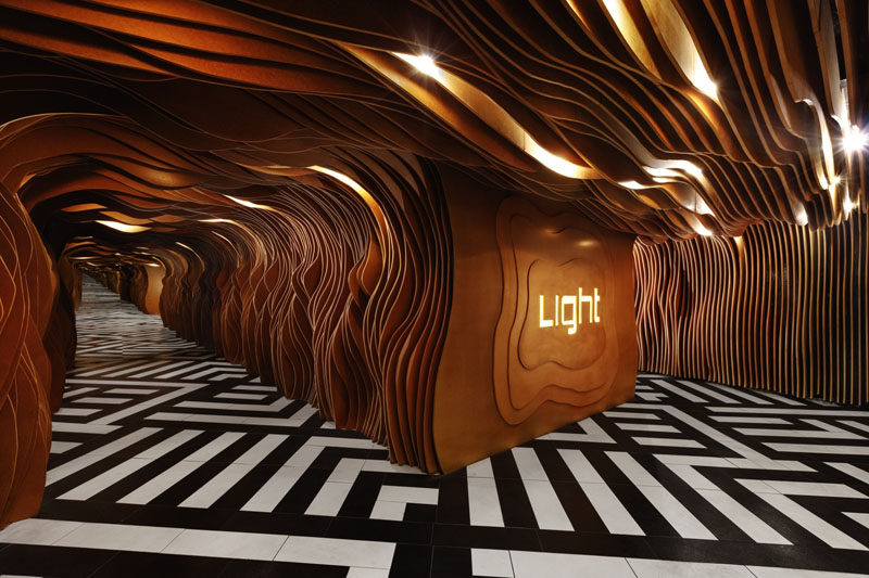 Inside the entrance of this nightclub, wooden panels with organic curves and hidden lighting guide you through to the main space, while a mirror on the wall makes the space seem endless.
