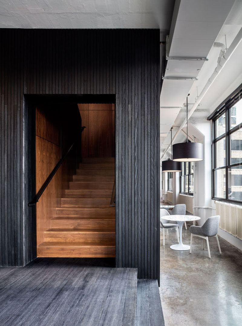 Blackened wood encases a dark walnut staircase in this office.