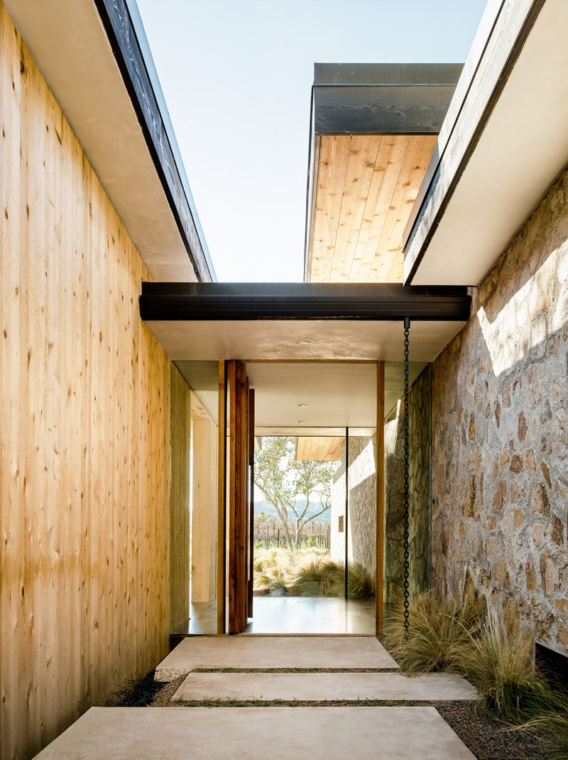 14 Modern Homes That Use Rain Chains To Divert Water // Sitting right at the front door, this rain chain made from a single black chain directs water away from the foundation of the home and creates a nice water feature when it rains.