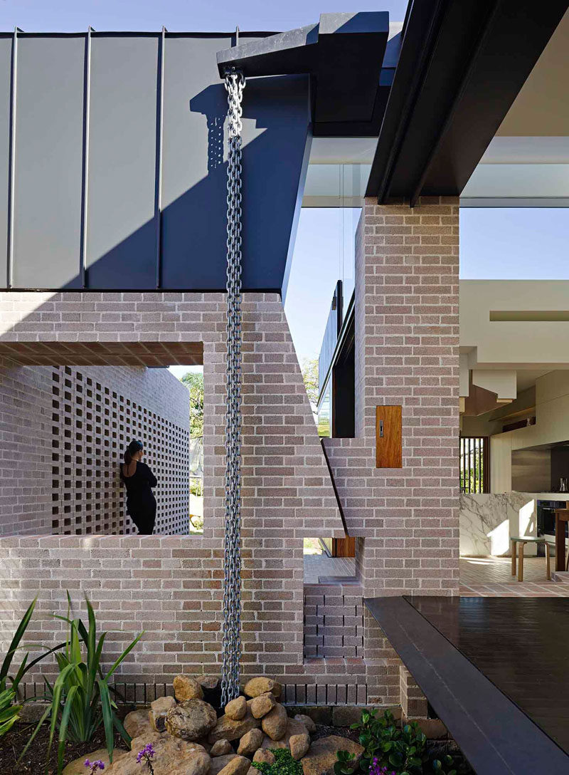 14 Modern Homes That Use Rain Chains To Divert Water // A number of chains hang from the roof of this home and guide the water into drainage disguised by a pile of rocks.