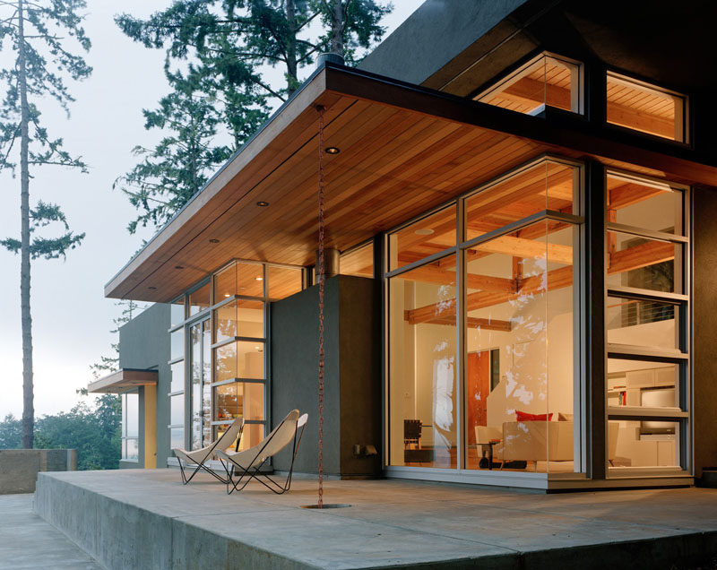 14 Modern Homes That Use Rain Chains To Divert Water // Chains hang from the roof of this house and flow into a hole in the cement that keeps the deck from becoming slippery when it rains.