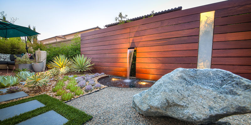 This garden has a mix of rocks, drought resistant plants, as well as a bit of grass to bring life into the yard. #RockGarden #GardenIdeas #ModernGarden #Landscaping #GardenDesign