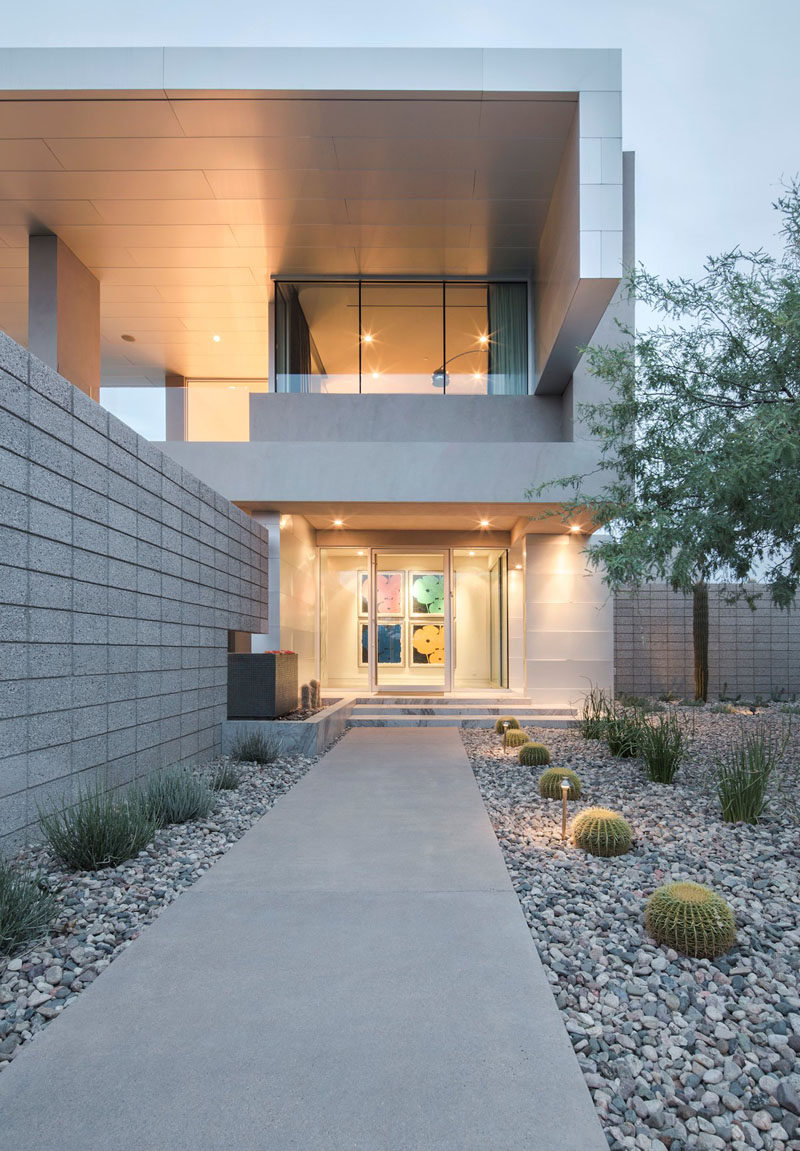 The entrance way and backyard of this home uses rocks and cacti to bring plant life in and watering responsibilities out.  #RockGarden #GardenIdeas #ModernGarden #Landscaping #GardenDesign