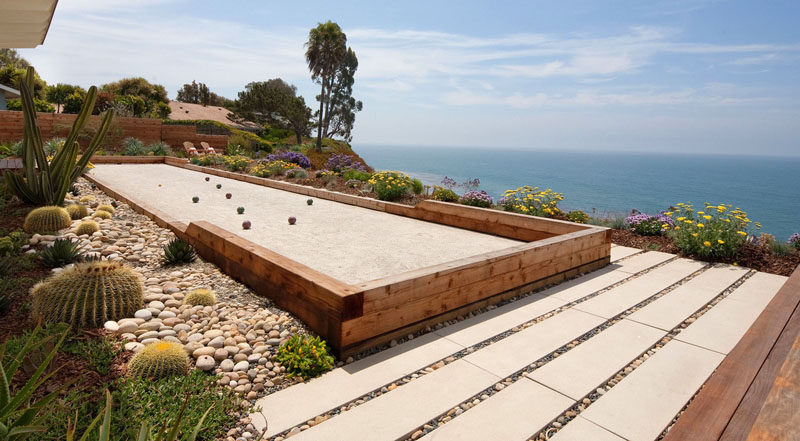 This backyard overlooking the ocean has a rock garden full of cacti and a long strip of gravel designed specifically for playing bocce. #RockGarden #GardenIdeas #ModernGarden #Landscaping #GardenDesign #BocceCourt
