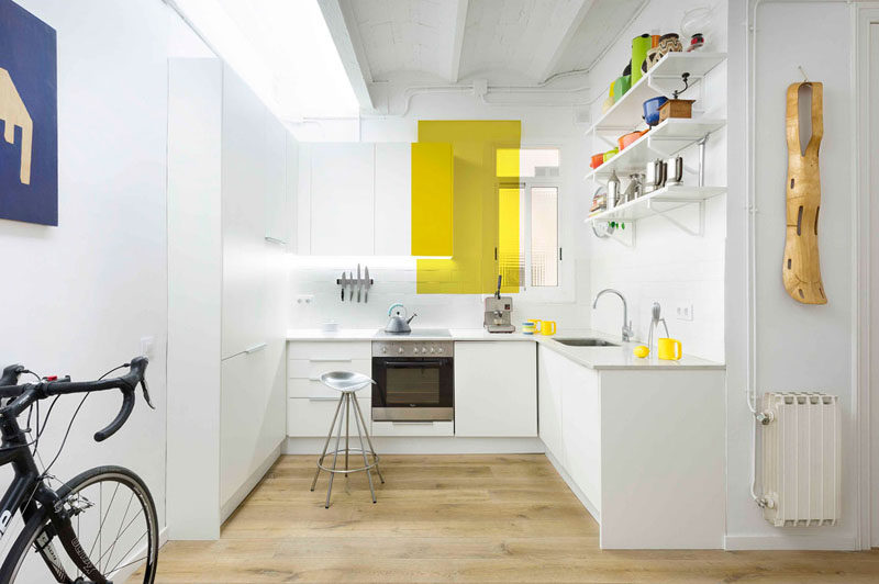 Kitchen Design Ideas - 14 Kitchens That Make The Most Of A Small Space // White walls and a rectangular pop of yellow help brighten this kitchen and make it feel larger than it actually is.