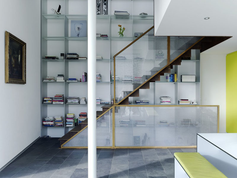 Stairs Design Ideas - 12 Examples Of Staircases With Bookshelves // The floor-to-ceiling bookshelf allows for lots of storage in this open concept home.