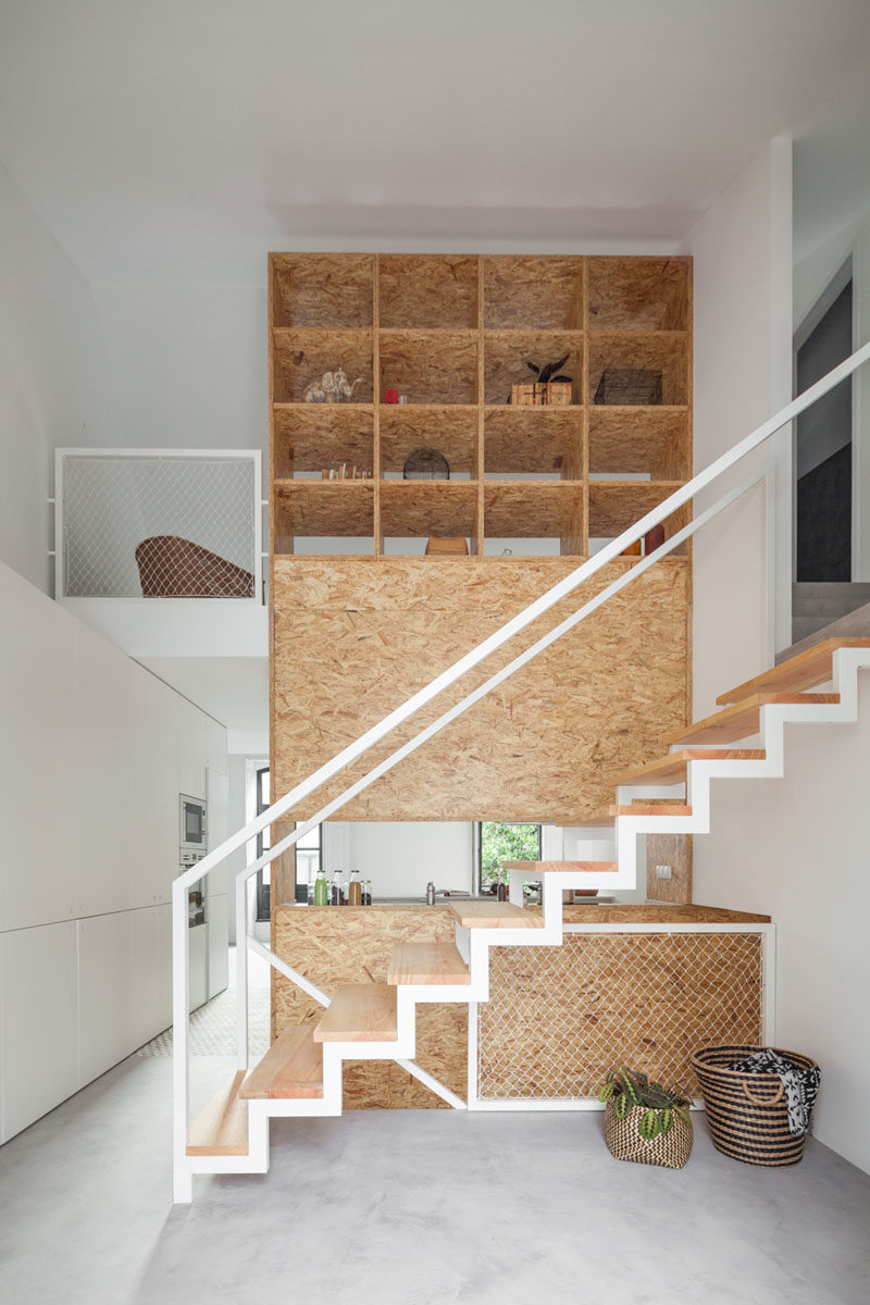 Stairs Design Ideas - 12 Examples Of Staircases With Bookshelves // A wooden wall transforms into an open bookshelf as you climb these stairs.