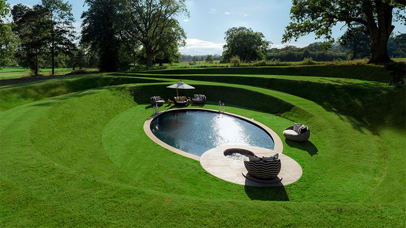 This outdoor space has a circular grassy path that leads to a sunken swimming pool.
