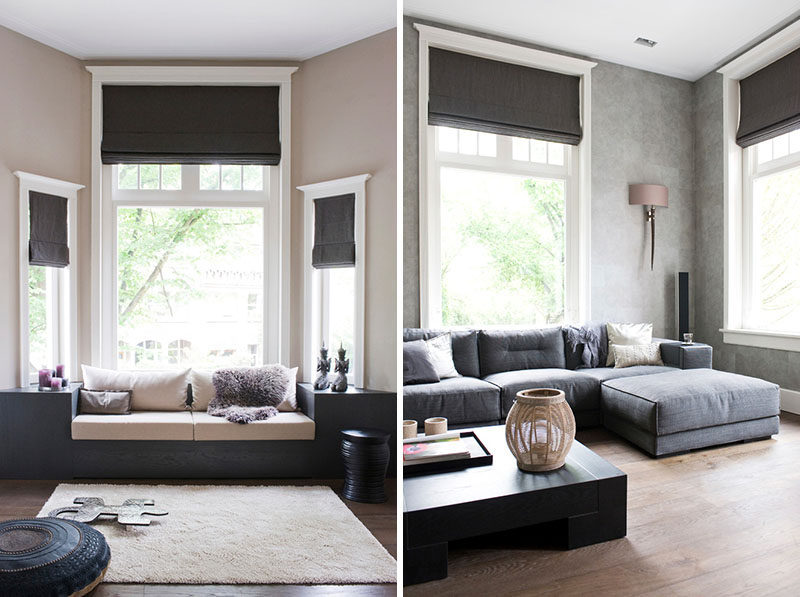 Black roman blinds draw attention to the tall ceilings in this living room.
