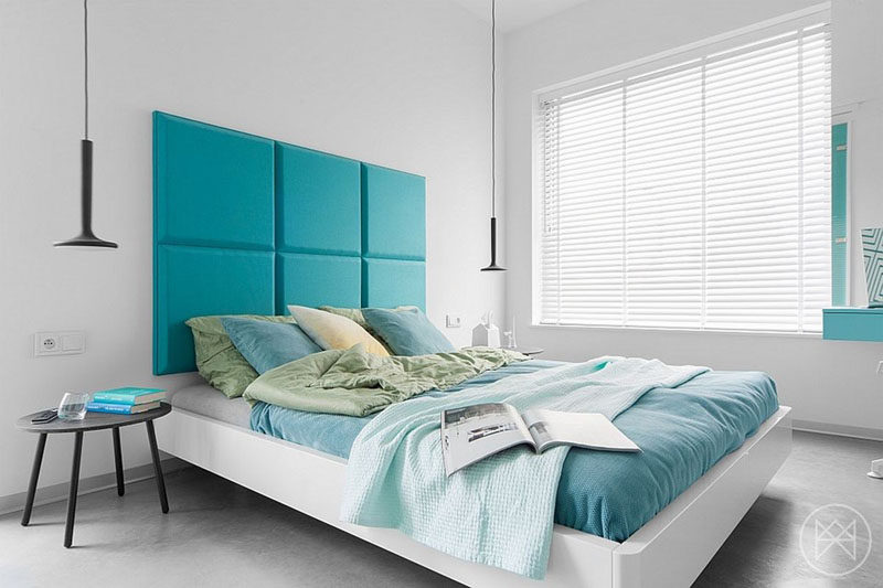 White Venetian blinds cover the large window in a modern bedroom.