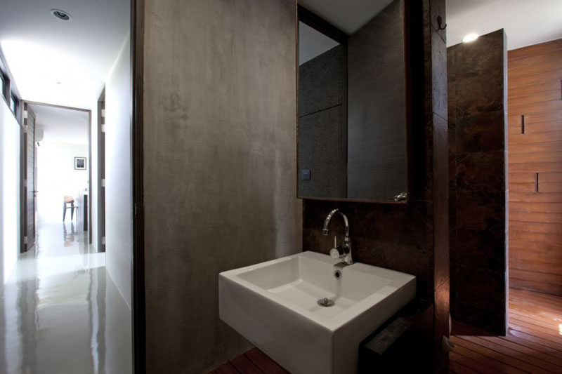 Concrete has been combined with wood and stone for an earthy look in this bathroom.