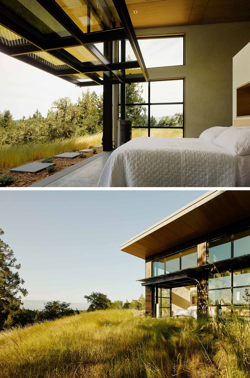 This bedroom opens up to the outdoors via a large glass paneled door on a pulley system.