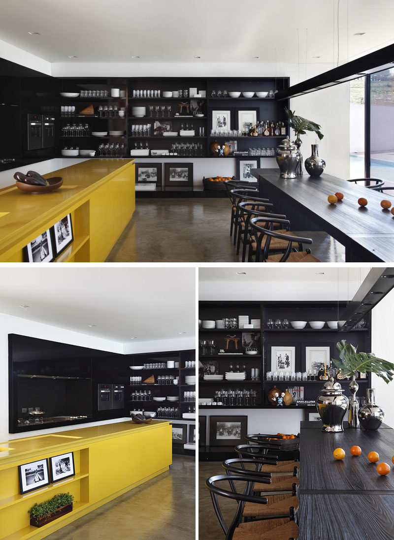 A yellow kitchen island adds a bright pop of color to the otherwise black cabinetry and shelving in the rest of the kitchen.
