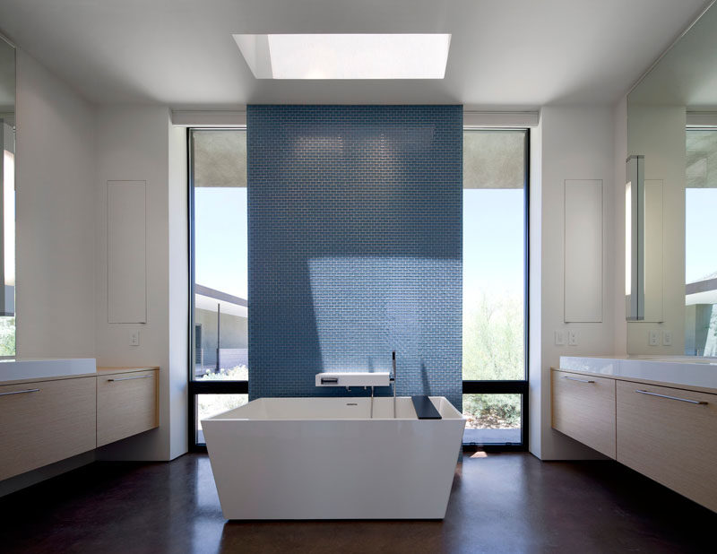 In this bathroom, tall windows and a skylight fill the space with natural light, while the blue tiled feature wall provides a focal point and privacy for when someone's taking a bath.