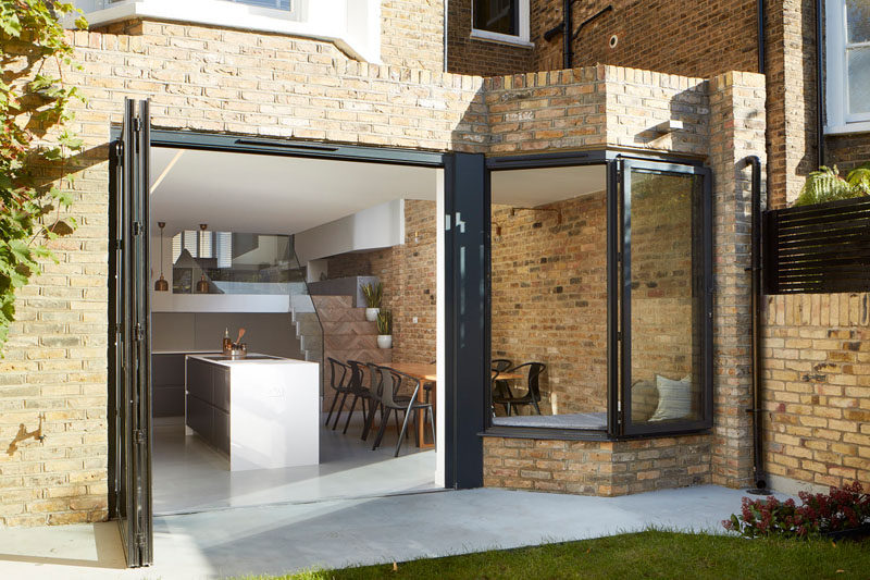 In this renovated british home, large folding doors and a window all open up to the backyard, ideal for indoor/outdoor living.