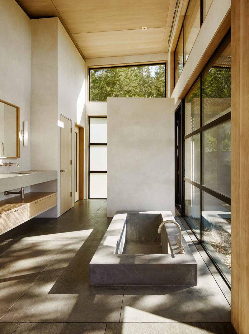 This bathroom has a sunken built-in concrete bathtub.