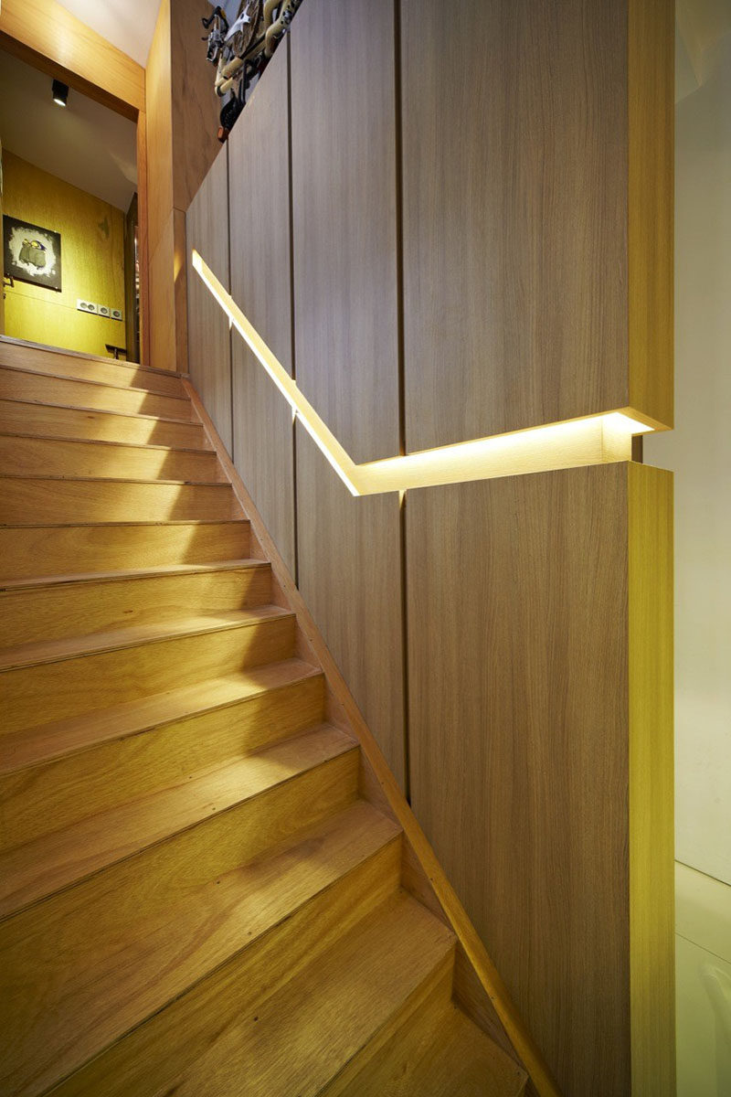 Stair Design Ideas - 9 Examples Of Built-In Handrails // In this Singaporean home, a wooden wall is broken up by the built-in handrail that features hidden lighting. #BuiltInHandrail #HandrailIdeas #HandrailDesign #StairDesign #Handrails