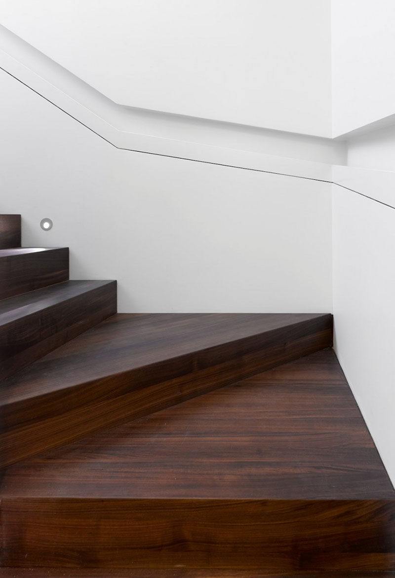Stair Design Ideas - 9 Examples Of Built-In Handrails // This white wall that wraps around the stairs has a section cut-out of it to house the handrail.  #BuiltInHandrail #HandrailIdeas #HandrailDesign #StairDesign #Handrails