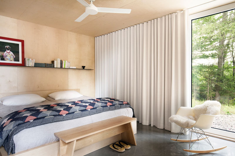 In this bedroom, light wood and soft white curtains help to warm the space up.