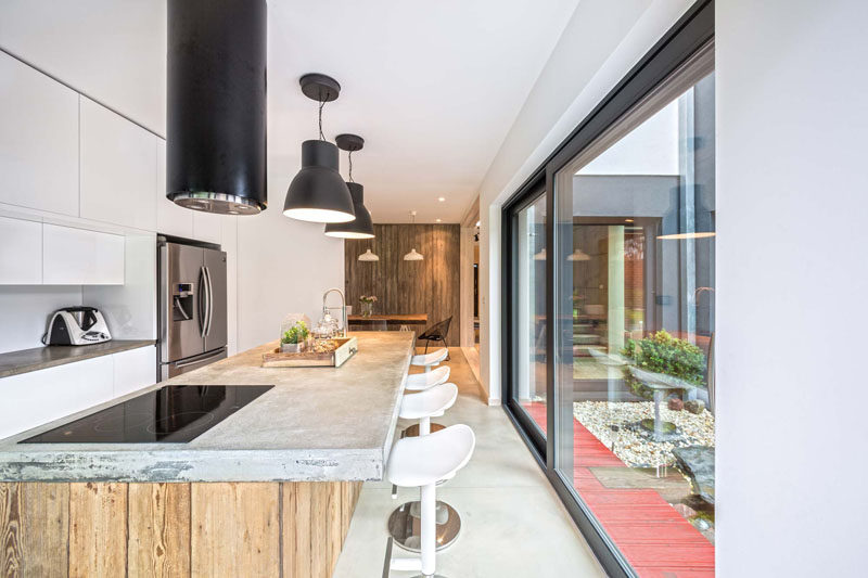 In this contemporary kitchen, a long concrete and wood island has ample room for seating and plenty of prep space. Large glass sliding doors give the kitchen access to the backyard.