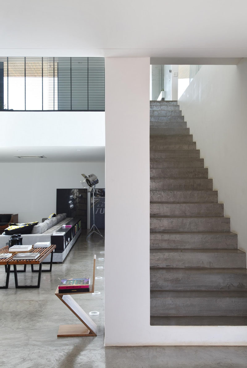 Concrete stairs are tucked behind the living area in this house.