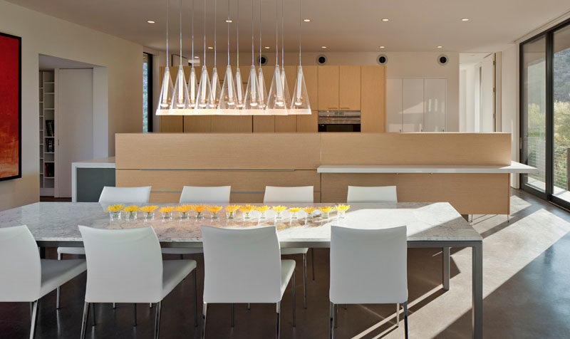 A collection of pendant lights help to anchor the dining table in this open space.