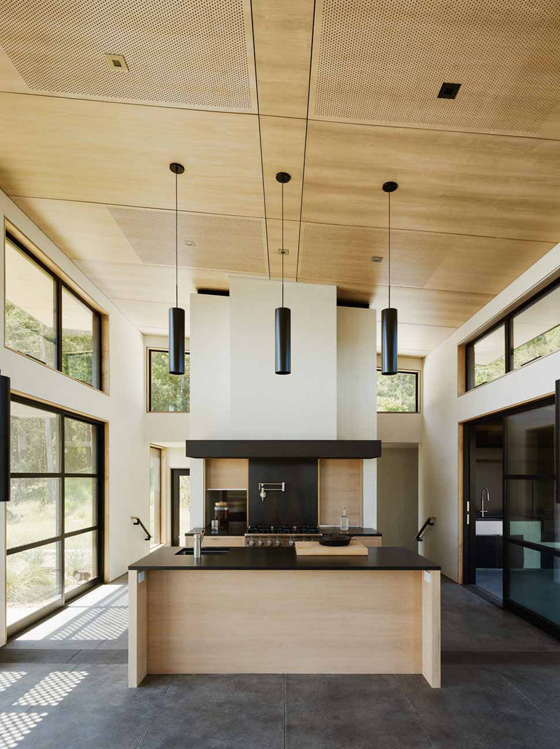 High ceilings and lots of windows let plenty of light into this wooden kitchen. Black accents match the window and door frames surrounding the kitchen.
