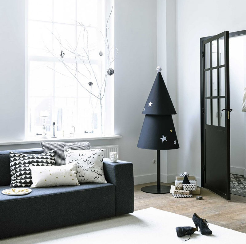 Christmas Decor Ideas - 14 DIY Alternative Modern Christmas Trees // A black fabric tree decorated with fabric paint and a pom pom topper puts a modern Scandinavian twist on the traditional Christmas tree.