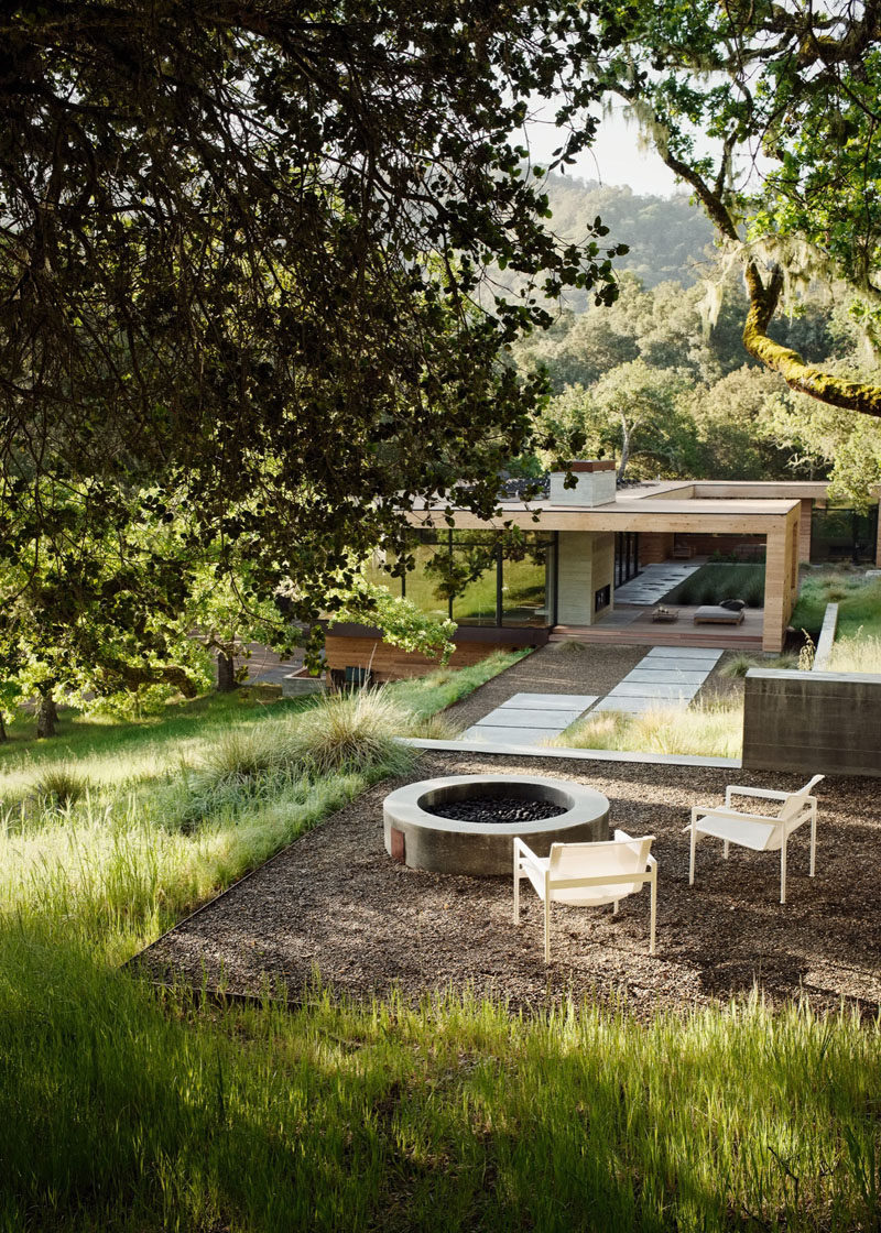This home has a firepit that's reached by a landscaped path.