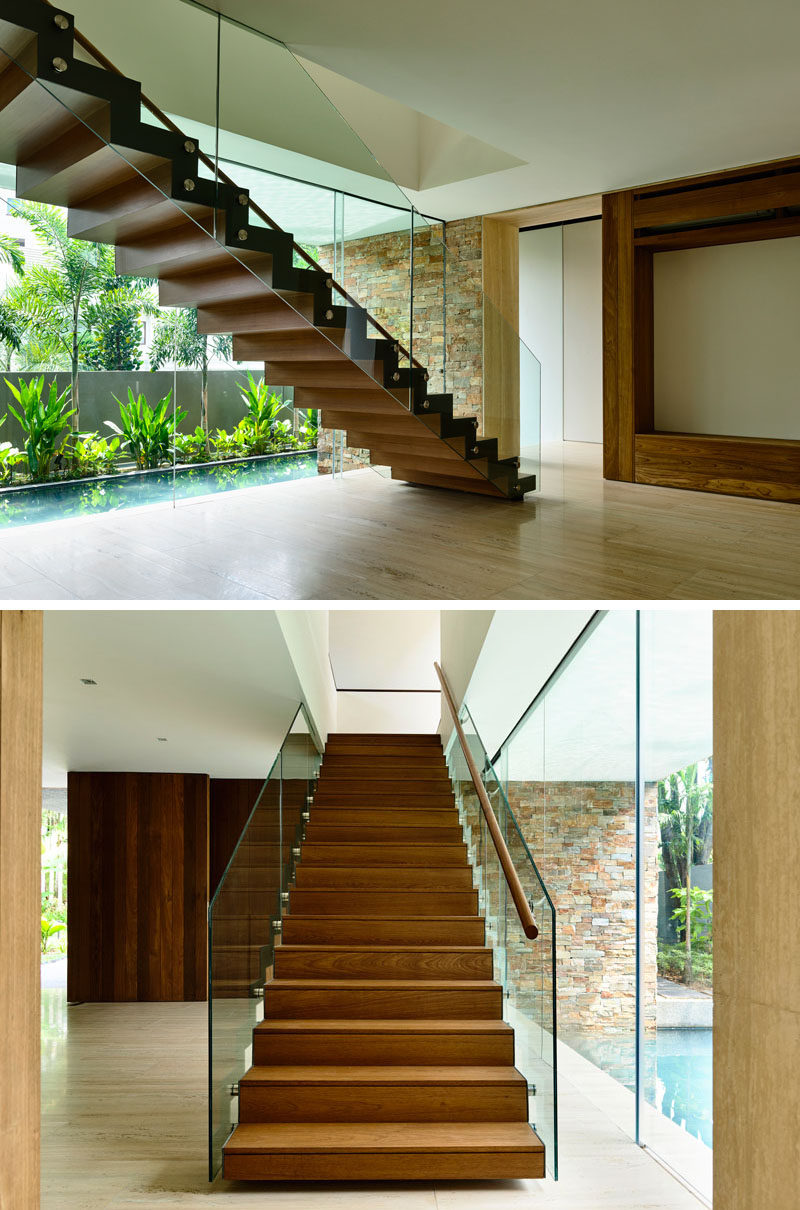 This Singaporean home has wooden stairs with a glass railing.