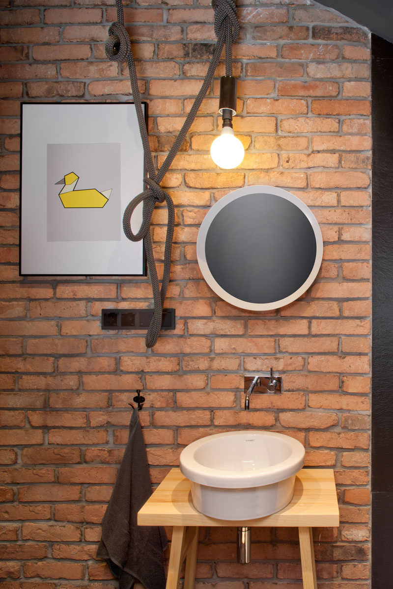 In this guest bathroom, a brick feature wall has been paired with a light hanging from a rope for a more industrial look.
